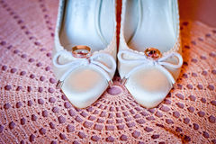 Wedding rings and shoes. White shoes of the bride with rings on pink stock image