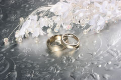 Wedding rings on silver background. Wedding bands on silvery background with white flowers and beads stock photos