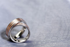 Wedding rings on silver cloth with copy space. Pair of red gold and platinum wedding rings on silver cloth with copy space, shallow depth of field Stock Photography