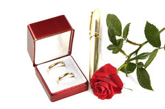 Wedding rings, small red rose and pen. Royalty Free Stock Photos