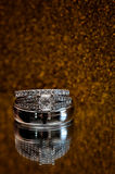 Wedding Rings. Sparkly wedding rings against a mirror with gold sparkle Royalty Free Stock Image