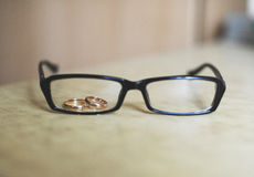 Wedding rings and spectacles. Wedding rings through an eyepiece of points Royalty Free Stock Image