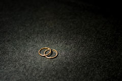 Wedding rings with spot gold light. Idea of gold wedding rings on dark background Royalty Free Stock Photos