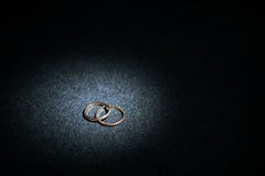 Wedding rings with spot light. Idea of gold wedding rings on dark background Royalty Free Stock Images