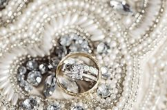 Wedding rings on sequins and pearls Royalty Free Stock Image