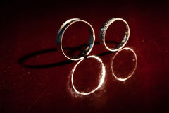 Wedding rings are stand a red background Stock Photo