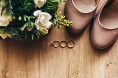 Wedding rings with stones on a wooden floor next to shoes and a. On a wooden floor a wedding bouquet with green leaves, white and yellow flowers, wedding rings Stock Images