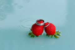 Wedding Rings and Strawberries. Wedding Rings, strawberries and the wet rainy table Royalty Free Stock Images