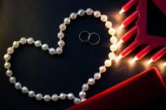 Wedding rings, a string of pearls on a black background, burning lights, a red box. St. Valentine`s Day Stock Images