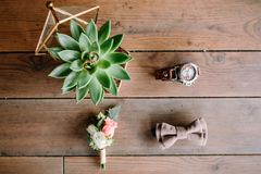 Wedding rings with succulent in glassed box, watch and boutonniere on wooden background. Flat lay. Top view Stock Photo