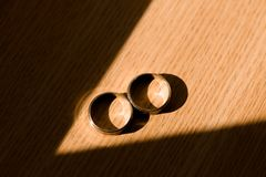 Wedding rings in sun light. Two wedding rings in sun light with shadow around them Royalty Free Stock Images