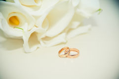 Wedding rings on the table on the background of the bride's bouq Stock Photo