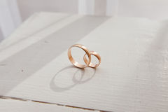 Wedding rings on the table. Gold wedding rings on a white table in the sun Stock Photos
