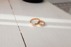Wedding rings on the table. Gold wedding rings on a white table in the sun Royalty Free Stock Photography