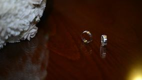Wedding rings are on the table. Two rings on the wooden background stock footage