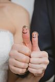 Wedding rings on their fingers painted with the Stock Photo