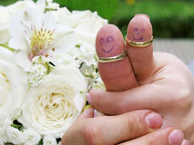 Wedding rings on their fingers people marrieds bride and groom, painted funny little men Stock Photos