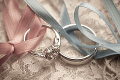 Wedding rings tied with blue and pink ribbons Royalty Free Stock Photos