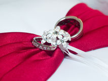 Wedding rings tied to pillow. A pair of silver wedding rings tied to a white ringbearer's pillow, sitting on top of a red bow Stock Photos