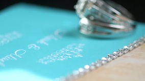 Wedding. Rings on top of invitation in blue color with stones stock footage