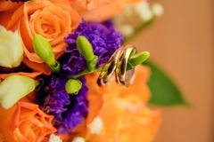 Pair of golden wedding rings inside bridal bouquet. Symbol of love and marriage on orange roses and eustoma (or Lisianthus). Tradi. Wedding rings on the twig of Royalty Free Stock Image
