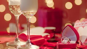 Wedding rings and two glasses filled with champagne. With bokeh lights and valentines on the background stock video