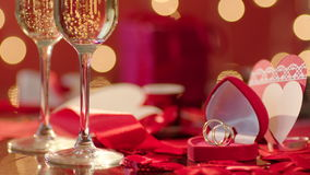 Wedding rings and two glasses filled with champagne. With bokeh lights and valentines on the background stock footage
