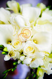 Wedding rings. Two wedding rings lie on a bouquet of white roses.  Rings are golden Stock Images
