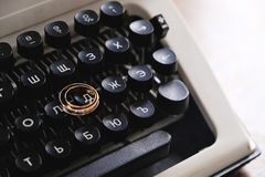 Wedding rings on the typewriter. Wedding rings placed on an ancient typewriter letter buttons royalty free stock photography