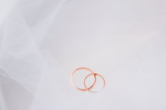 Wedding rings on veil. Two golden wedding rings on white veil royalty free stock photography