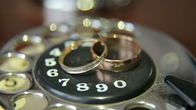Wedding rings on vintage phone, close-up. Wedding rings lie on the dial of the ancient phone, close-up stock footage