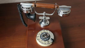 Wedding rings on vintage phone, close-up. Two rings lie on a retro telephone on wood background. Movement from top to bottom stock video footage