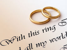 Wedding rings and vow. Two wedding rings on a paper with text of wedding vow