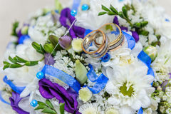 Wedding rings on wedding bouquet. Wedding rings and beautiful summer wedding bouquet.  Delicate bright flowers for girls Stock Photos