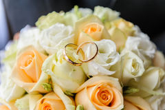 Wedding rings on wedding bouquet. Beautiful summer wedding bouquet of white and pink roses and wedding rings.  Delicate bright flowers for girls Stock Photos