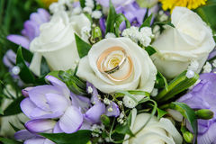 Wedding rings on wedding bouquet. Wedding rings and beautiful summer wedding bouquet of white roses and purple rocuses. Delicate bright flowers for girls Royalty Free Stock Image