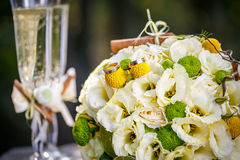 Wedding rings with wedding bouquet from beige roses, cinnamon, a lemon, a lime and glasses of champagne Stock Photos