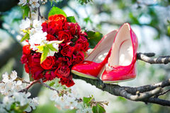 Wedding rings, wedding bouquet and the bride's shoes on the tree Royalty Free Stock Image