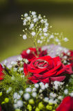 Wedding rings and wedding bouquet. Of red roses Royalty Free Stock Photo