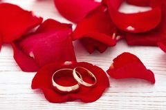 Wedding rings and wedding bouquet of red roses petals. Wedding rings and wedding bouquet of red roses on wooden table. horizontally Royalty Free Stock Photography