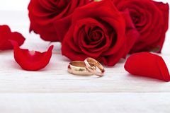 Wedding rings and wedding bouquet of red roses petals. Wedding rings and wedding bouquet of red roses on wooden table. horizontally Stock Photos