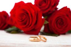 Wedding rings and wedding bouquet of red roses. On wooden table. horizontally Stock Photo