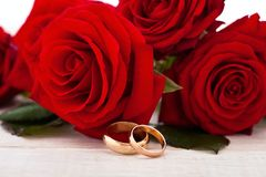 Wedding rings and wedding bouquet of red roses. Wedding rings and wedding bouquet of red roses on wooden table. horizontally Royalty Free Stock Photos