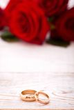 Wedding rings and wedding bouquet of red roses. Wedding rings and wedding bouquet of red roses on wooden table. horizontally Stock Image