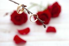 Wedding rings and wedding bouquet of red roses. On wooden table. horizontally Royalty Free Stock Images
