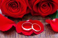 Wedding rings and wedding bouquet of red roses. On wooden table. horizontally Stock Photos