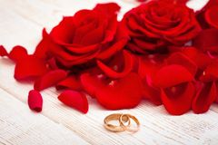 Wedding rings and wedding bouquet of red roses. On wooden table. horizontally Royalty Free Stock Photography