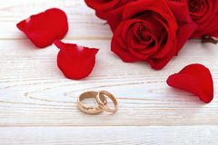 Wedding rings and wedding bouquet of red roses. On wooden table. horizontally Stock Image