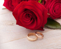 Wedding rings and wedding bouquet of red roses. On wooden table. horizontally Stock Photography