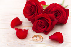 Wedding rings and wedding bouquet of red roses. On wooden table. horizontally Stock Images